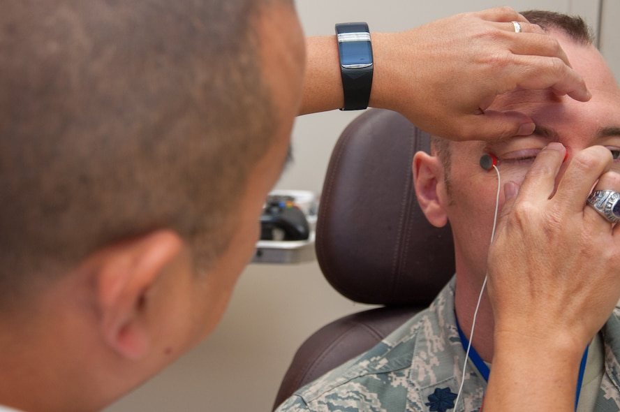 Dino Tsuchiyama (left), Aeromedical Consultation Service Ophthalmology Branch electro-diagnostic technician, attaches electrodes to Lt. Col. Christopher Cannon in order to measure how well the retinas in Cannon's eyes react to light. Ophthalmological electrophysiology studies the electrical activity of the eyes. (U.S. Air Force photo/John Harrington)