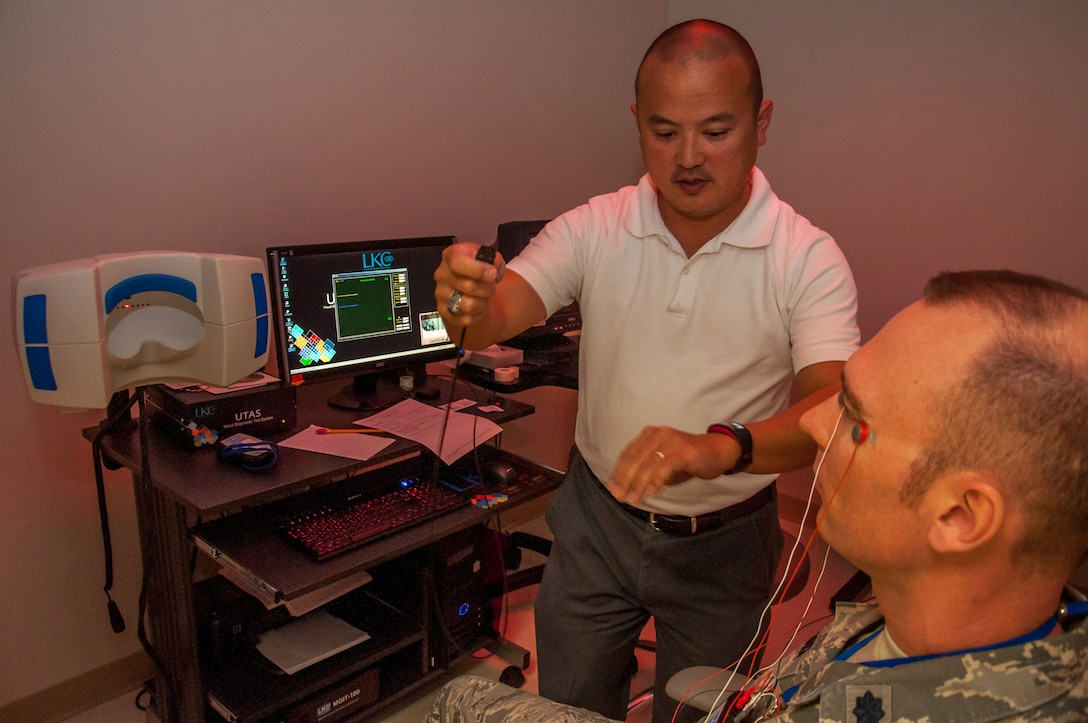 Dino Tsuchiyama (left), Aeromedical Consultation Service Ophthalmology Branch electro-diagnostic technician, attaches electrodes from Lt. Col. Christopher Cannon to a multifocal electroretinogram machine. The machine measures electrical activity in the retina when the eye is exposed to a light source. (U.S. Air Force photo/John Harrington)