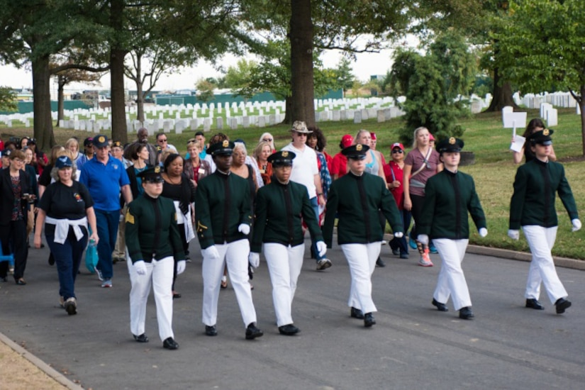 Men and women walk in a group through Arlington National Cemetery.