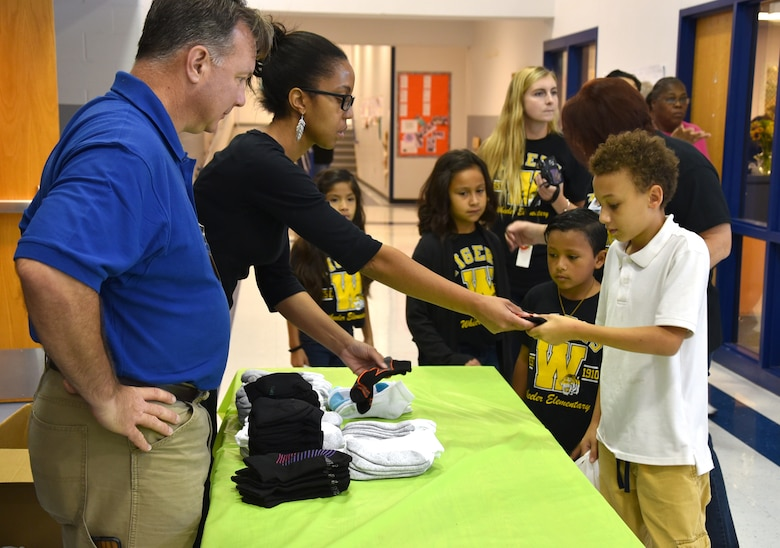 Joe Angermeier and Quinn Green, program managers with the 38th Cyberspace Engineering Group's Requirements Implementation Section, hand out a new pair of socks to students at Wheeler Elementary Oct. 6.