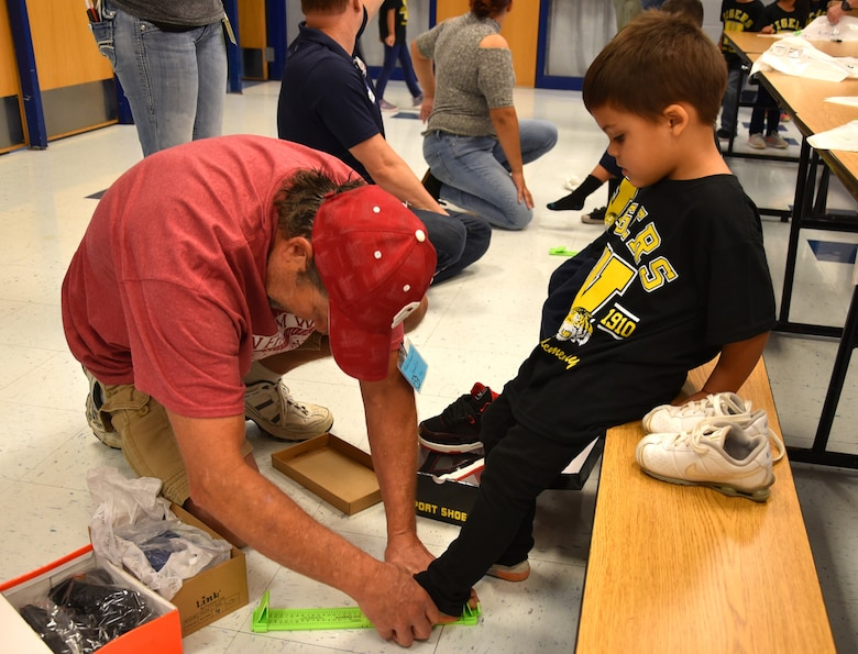 John Ide measures the foot of a Wheeler Elementary student Oct. 6. Ide, a program manager with the 38th Cyberspace Engineering Group's Requirements Implementation Section, was one of the volunteers on hand at the elementary school to help distribute new shoes and socks to the 400 students.
