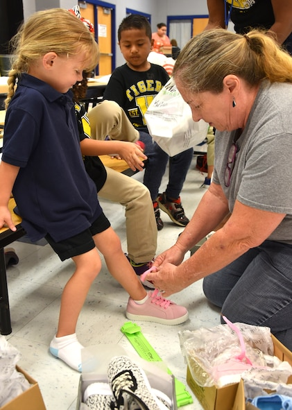 Vicki Morrison, a 38th Cyberspace Engineering Group Requirements Implementation Section program manager, checks the fit on a new pair of pink shoes for a Wheeler Elementary School student.