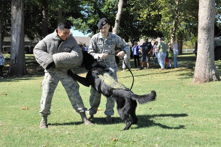 Military Working Dog Kali and handler Staff Sgt. James Stiegler, 72nd Security Forces Squadron, perform a routine demonstration to a crowd during the 3rd annual Heritage Day celebration, commemorating the 75 years of partnership between the city of Midwest City and Tinker Air Force Base.