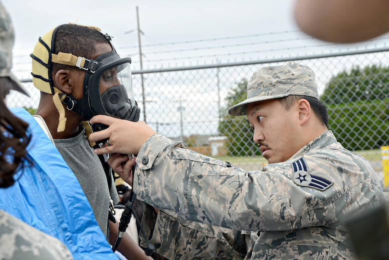 Senior Airman Heaven Yang, with the 72nd Aerospace Medicine Squadron, helps secure the gas mask for Corey Morgan, with 72nd ABW Civil Engineering Directorate Emergency Management, before he enters a contaminated environment during the Oct. 5 CBRNE exercise.