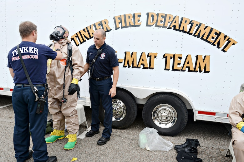 Lt. Chad Beals, left, and Capt. David Jones, right, help Lt. Jeff Briley, all with the Tinker Fire and Emergency Services, with his gas mask and Level B Hazmat suit. The suit helps keep liquids or chemicals off of the skin while working in the decontamination area of the chemical, biological, radiological, nuclear, explosive exercise Oct. 5.