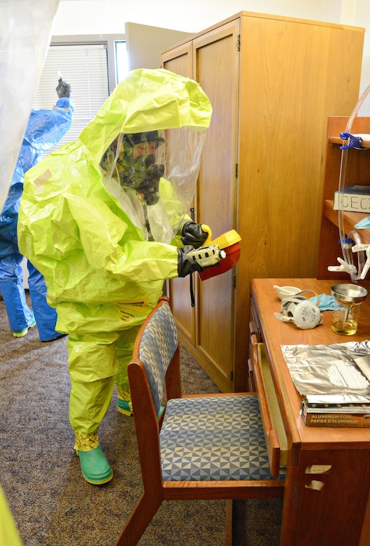 Senior Airman Kristina Song, with the 72nd Aerospace Medicine Squadron's Bioenvironmental Flight, monitors air quality in a simulated contaminated area during the Oct. 5 CBRNE exercise. Wearing a Level A Hazmat fully-encapsulated suit, Airman Song is able to communicate with her team, monitor the air, identify chemicals, take photos of the scene and take samples of liquids or powder if necessary