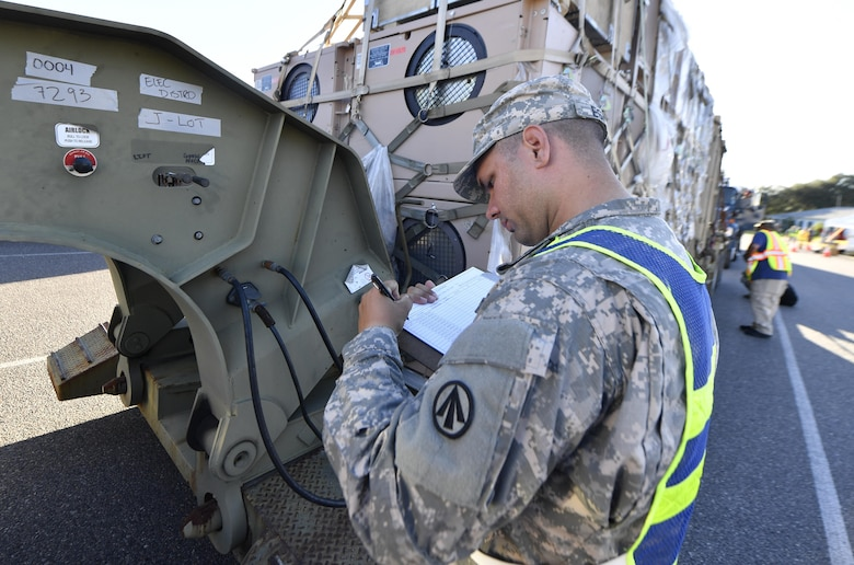 U.S. Army Sgt. Roberto Espino, 640 Transportation Det. Tampa, Florida, inspects equipment as it arrives at an initial staging area here Oct. 20.