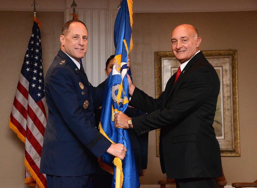 Air Force Sustainment Center Commander Lt. Gen. Lee K. Levy II exchanges the flag with Dennis D'Angelo, the new director for the 448th Supply Chain Management Wing, in a formal Change of Leadership ceremony Oct. 17 at the Tinker Club.
