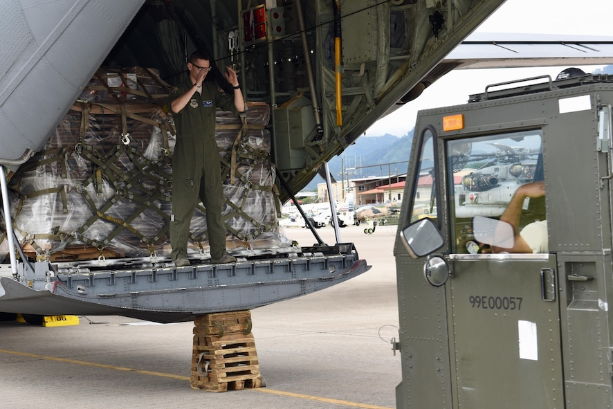 Senior Airman David Heinz, a loadmaster from the 40th Airlift Squadron, directs an air transporter from the 612th Air Base Squadron, driving a K-loader toward the C-130J.  Heinz worked with the air transporters to offload the pallets during a routine global channel mission Oct. 18, 2017 to Soto Cano Air Base, Honduras, delivering sustainment and supplies to Airmen supporting Joint Task Force Bravo.  The Airmen from the 317th Airlift Wing at Dyess Air Force, Texas, routinely support the Honduras mission, a tasking from the 618th Air Operations Center.  (Air Force photo by Master Sgt. Kristine Dreyer)