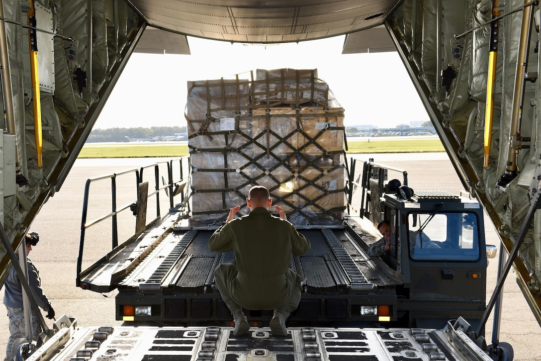 Senior Airman David Heinz, a loadmaster from the 40th Airlift Squadron, directs an air transporter at Charleston Air Force Base, S.C., while loading pallets destined for Soto Cano Air Base, Honduras, Oct. 18, 2017.  A C-130J crew from the 317th Airlift Wing at Dyess Air Base, Texas, completed a routine global channel mission delivering sustainment and supplies to Airmen supporting Joint Task Force-Bravo. Airmen from Soto Cano rely on the mission to bring items needed to complete their mission while stationed in Central America.