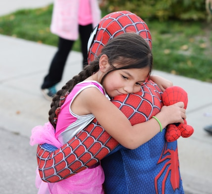 Senior Airman Dorukhan Reels, a response force leader assigned to the 28th Security Forces Squadron, hugs Emmalyn Jensen, daughter of Staff Sgt. Michael Jensen, a cyber transport systems technician assigned to the 28th Communications Squadron, during a Superhero Parade at Ellsworth Air Force Base, S.D., Oct. 11, 2017.This is just one of eight events that are happening on base where 28th SFS members are spreading awareness for Crime Prevention Month and are keeping Halloween safe and fun. (U.S. Air Force photo by Airman 1st Class Thomas Karol)