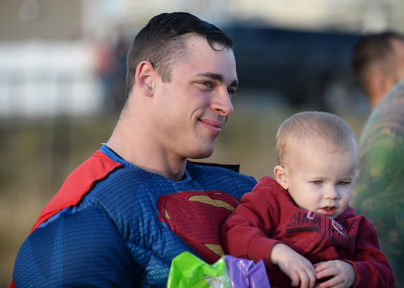 Staff Sgt. Tyler Perry, a security forces evaluator assigned to the 28th Security Forces Squadron, holds a child for a picture at Ellsworth Air Force Base, S.D., Oct. 11, 2017. Local police and 28th SFS members posed for pictures, handed out candy and raised awareness about Crime Prevention Month during a superhero parade. (U.S. Air Force photo by Airman 1st Class Thomas Karol)