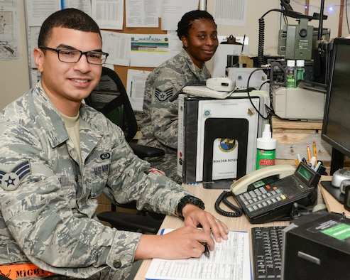 U.S. Air Force Senior Airman Johan Pena, foreground, junior controller and Staff Sgt. Takneisha Boatright, senior controller, both assigned to the 8th Expeditionary Air Mobility Squadron/Air Mobility Command Center, sit at their computers in the AMCC at Al Udeid, Air Base, Qatar, Aug. 22, 2017.