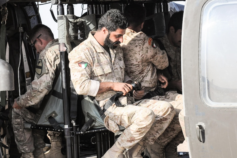 Three soldiers sitting in a helicopter.