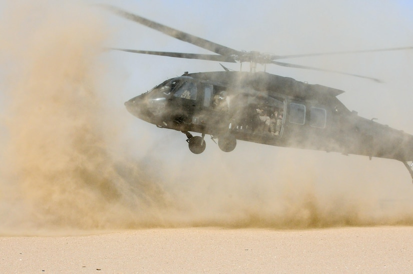 Helicopter takes off, stirring up a cloud of dust.