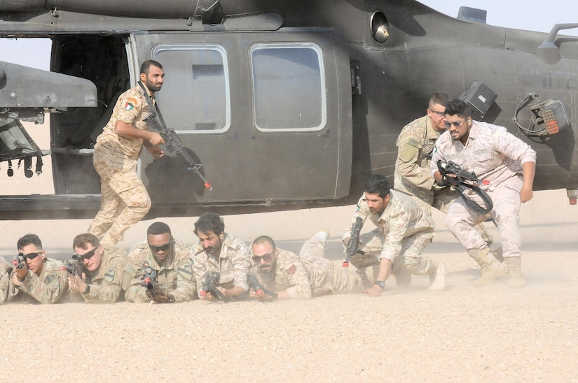 U.S. and Kuwaiti soldiers in position on the ground in front of a helicopter.