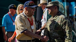 U.S. Marine veteran Ralph Simoneau from the 5th Marine Division shakes hands with Garrison Commander, Lt. Col. Cristopher Marquez.