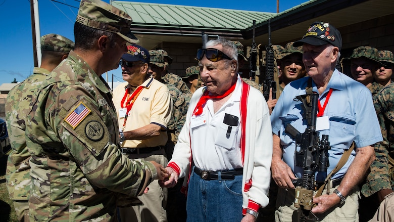 U.S. Marine veteran Duane Tunnyhill of the 5th Marine Division shakes hands with Garrison Commander, Lt. Col. Cristopher Marquez.