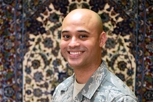 An airman poses for a photo in front of a patterned surface.