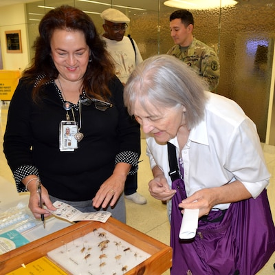 Graciela Alfano, licensed vocational nurse, shows Joann Dick different insects that can cause various allergy reactions during the Military Retiree Appreciation Day at Brooke Army Medical Center Medical Mall Oct. 14. BAMC had more than 70 specialty care clinics and 40 informational tables consisting of representatives from medical clinics at Fort Sam Houston, organizations and agencies serving veterans and retirees. At the health fair, free flu shots and immunizations and walk-in mammograms were also provided and prescription eyeglasses were ordered for retirees who had less than a year old prescriptions.