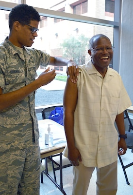 Airman 1st Class Salen Orange gives a flu shot to Craig Bernard during the Military Retiree Appreciation Day at Brooke Army Medical Center Medical Mall Oct. 14. BAMC had more than 70 specialty care clinics and 40 informational tables consisting of representatives from medical clinics at Fort Sam Houston, organizations and agencies serving veterans and retirees. At the health fair, free flu shots and immunizations and walk-in mammograms were also provided and prescription eyeglasses were ordered for retirees who had less than a year old prescriptions.