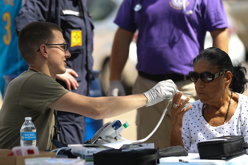 Army Spc. Jacob Parker, a health care specialist with the Ohio Army National Guard's 285th Medical Company, takes the vital signs of a patient at a temporary medical outreach station posted on a residential street in Juana Diaz, Puerto Rico, Oct. 21, 2017. Parker is part of a Rapid Assessment Team that travels to members of the community who need medical attention, but are unable to make it to a hospital or aid station due to road closures or lack of transportation following Hurricane Maria. Ohio Army National Guard photo by Sgt. Joanna Bradshaw