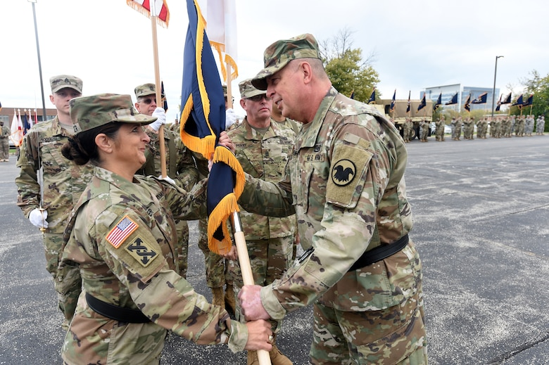 Army Reserve Brig. Gen. Kris A. Belanger, left, Commanding General, 85th Support Command, takes the command Colors from Maj. Gen. Scottie D. Carpenter, Deputy Commanding General, U.S. Army Reserve Command in an Assumption of Command ceremony at the 85th SPT CMD headquarters, October 21, 2017.