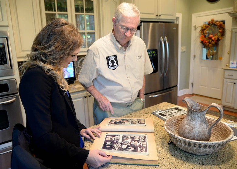 "Retired Lt. Col. Richard ""Gene"" Smith, former 50th Flying Training Squadron Commander, shows Courtney Cox, editor of Town and Gown magazine, documents and photos of when he was a prisoner of war, Oct. 17, 2017, in his home in West Point, Mississippi. Smith was shot down Oct. 25, 1967, and spent five and a half years as a POW. (U.S Air Force photo by Airman 1st Class Beaux Hebert)"