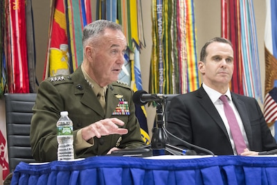 Marine Corps Gen. Joe Dunford speaks at a news conference while seated alongside Brett H. McGurk.