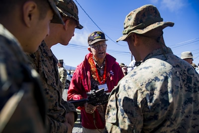 Louie Lepore, a veteran of the 5th Marine Division and Iwo Jima, talks to Marines from the 2nd Battalion, 3rd Marines, during a visit to Pohakuloa Training Area, Hawaii, Oct. 20, 2017. The veterans visited the training area as part of the 68th annual reunion of the 5th Marine Division Association and viewed weapons and equipment used by today's Marines. Marine Corps photo by Sgt. Ricky Gomez