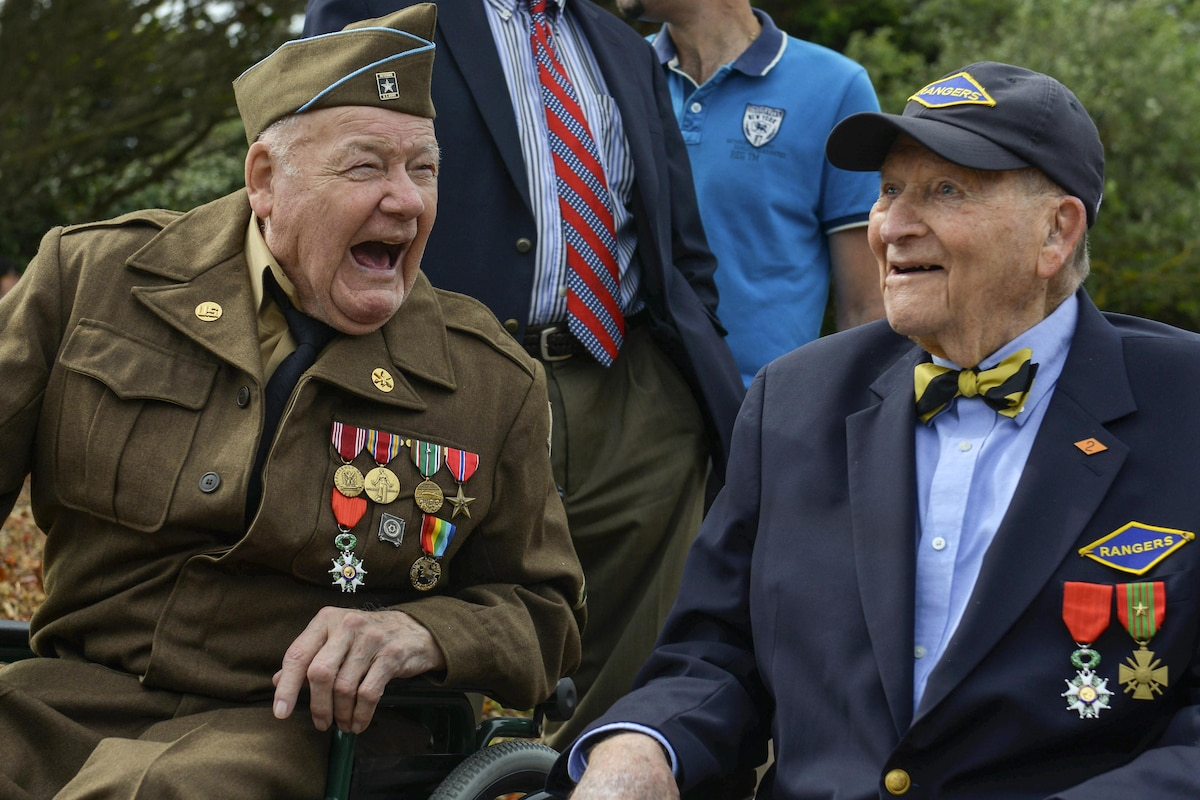 Two D-Day veterans laugh together.