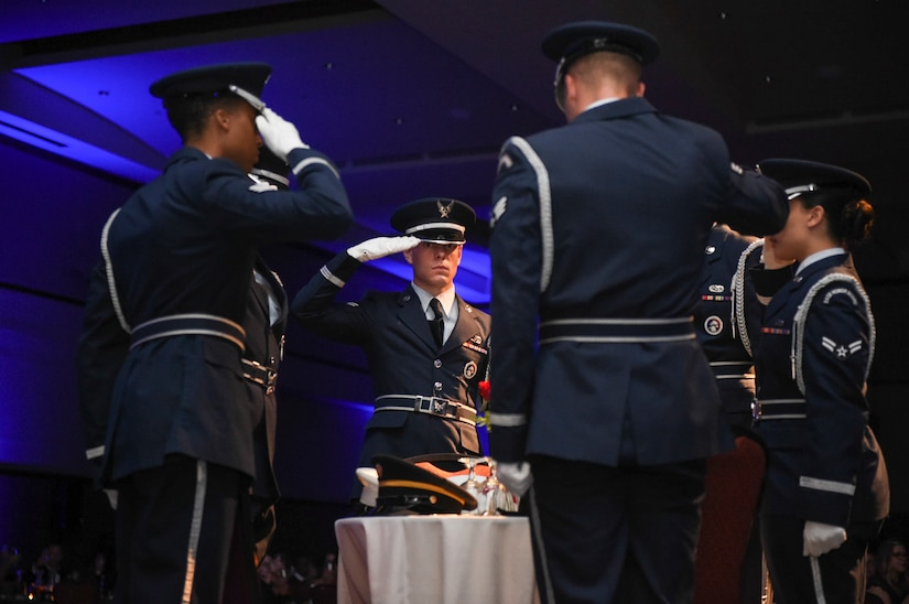 628th Force Support Squadron Honor Guardsmen salute the Prisoner of War, Missing in Action table at the Air Force Ball in the Charleston Area Convention Center in North Charleston, S.C., Oct. 21, 2017.
