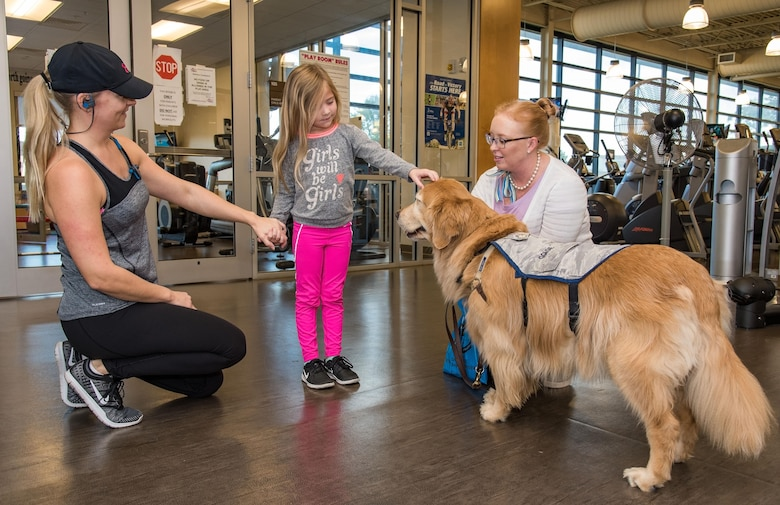 Addison Burrows, center, pets Lt. Col. Goldie, the only U.S. Air Force therapy dog visiting personnel on the base as part of Family Advocacy's Domestic Violence Awareness Month outreach, Oct. 19, 2017, at the Fitness Center on Dover Air Force Base, Del. Addison is the daughter of MaryAnne Burrows, pictured on the left, and Master Sgt. Chris Burrows, 436th Logistics Readiness Squadron. (U.S. Air Force photo by Roland Balik)