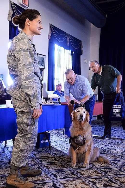 Maj. Regina Owen, 436th Medical Operations Squadron psychiatric mental health nurse practitioner, introduces Lt. Col. Goldie, a nine-year-old Golden Retriever therapy dog stationed at Walter Reed National Military Medical Center, Bethesda, Md., to local area military retirees, Oct. 21, 2017, at The Landings on Dover Air Force Base, Del. As part of Family Advocacy's outreach during Domestic Violence Awareness Month, Owen and Goldie stopped in during Dover AFB Retiree Day. (U.S. Air Force photo by Tech. Sgt. Matt Davis)