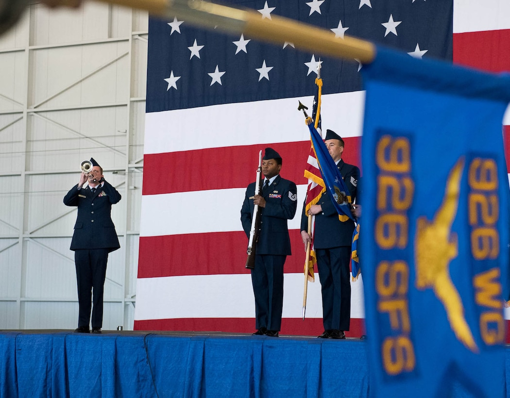 (Left) Tech. Sgt. Johnathon Lavender performs the national anthem on his trumpet as honor guard members present the colors during the 926th Change of Command ceremony on Oct. 14 at the Lightning hangar.