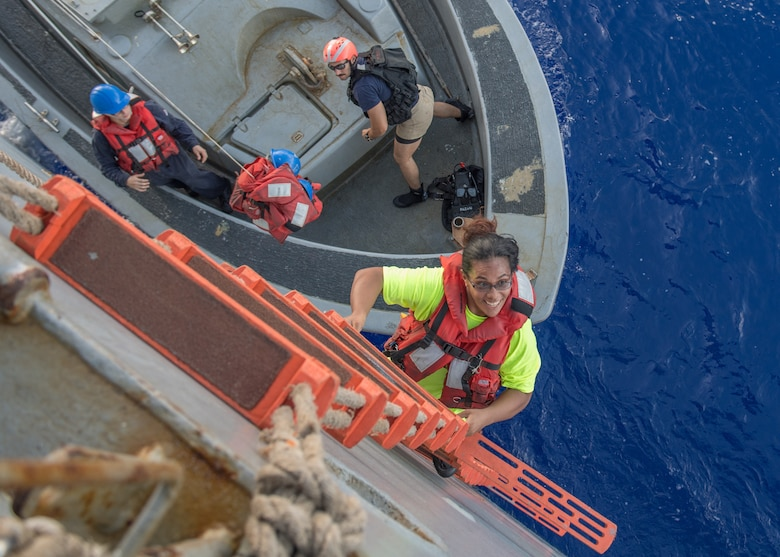 PACIFIC OCEAN (Oct. 25, 2017) Tasha Fuiaba, an American mariner who had been sailing for five months on a damaged sailboat, climbs the accommodation ladder to board the amphibious dock landing ship USS Ashland (LSD 48). Ashland, operating in the Indo-Asia-Pacific region on a routine deployment, rescued two American mariners who had been in distress for several months after their sailboat had a motor failure and had strayed well off its original course while traversing the Pacific Ocean.
