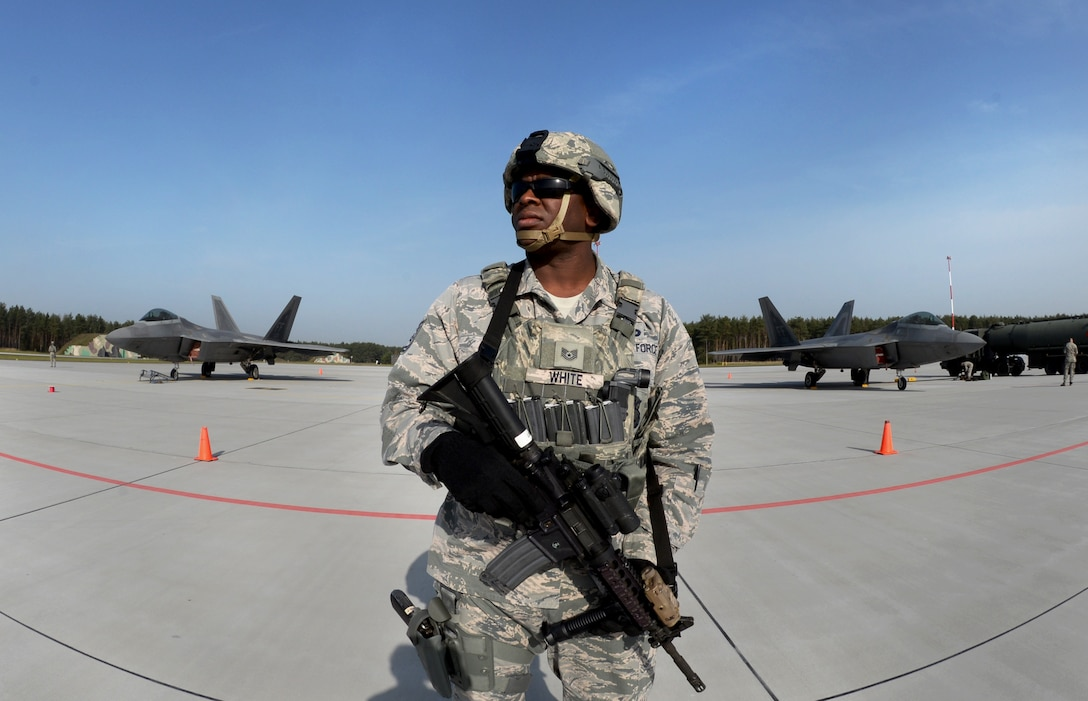 U.S. Air Force Tech. Sgt. Paul White, 633rd Security Forces Squadron flight chief, stands guard of F-22 Raptors from the 1st Fighter Wing, Joint Base Langley-Eustis, Va., Oct. 17, 2017, at Powidz Air Base, Poland. This forward deployment is an opportunity for the F-22s to train alongside U.S. and allied air force aircraft in a realistic training environment. (U.S. Air Force photo by Senior Airman Tenley Long)