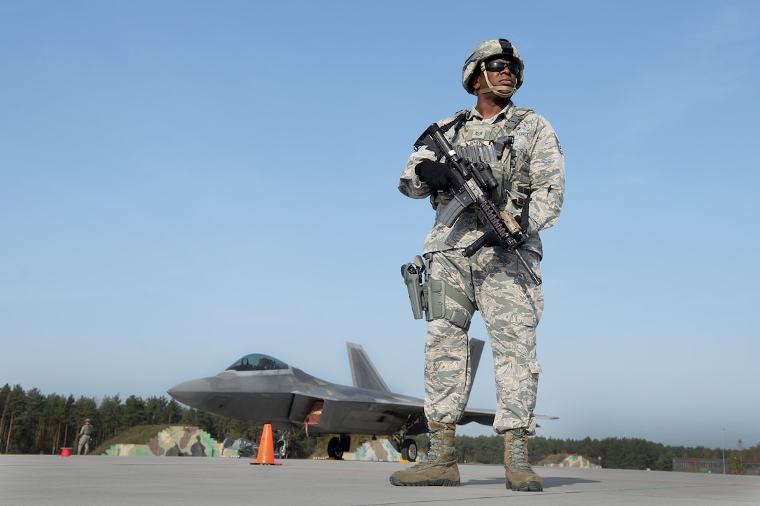 U.S. Air Force Tech. Sgt. Paul White, 633rd Security Forces Squadron flight chief, stands guard of an F-22 Raptor from the 1st Fighter Wing, Joint Base Langley-Eustis, Va., Oct. 17, 2017, at Powidz Air Base, Poland. This forward deployment is an opportunity for the F-22s to maximize training opportunities, demonstrate the U.S. Air Force's steadfast commitment to NATO allies and deter any actions that destabilize regional security. (U.S. Air Force photo by Senior Airman Tenley Long)
