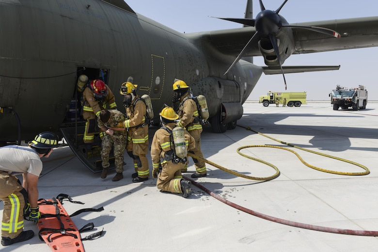 U.S. Air Force firefighters assigned to the 379th Expeditionary Civil Engineering Squadron assist a Royal Air Force member, simulating a casualty, from a C-130J Hercules at Al Udeid Air Base, Qatar, Oct. 3, 2017.