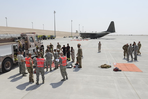 Members of the U.S. Air Force, Royal Air Force, and Qatar Emiri Air Force take part in responding too, and evaluating the response too, a simulated aircraft accident on the runway at Al Udeid Air Base, Qatar, Oct. 3, 2017.
