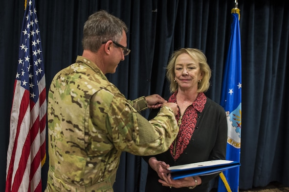 Col. Stewart Hammons, 27th Special Operations Wing commander, presents Janet Day, 27th SOW secretary, with the Outstanding Civilian Career Service Award during Day's retirement ceremony Sept. 29, 2017, at Cannon Air Force Base, New Mexico. Day served 32 years to the Air Force, 29 of them here at Cannon. (U.S. Air Force photo by Senior Airman Luke Kitterman/Released)