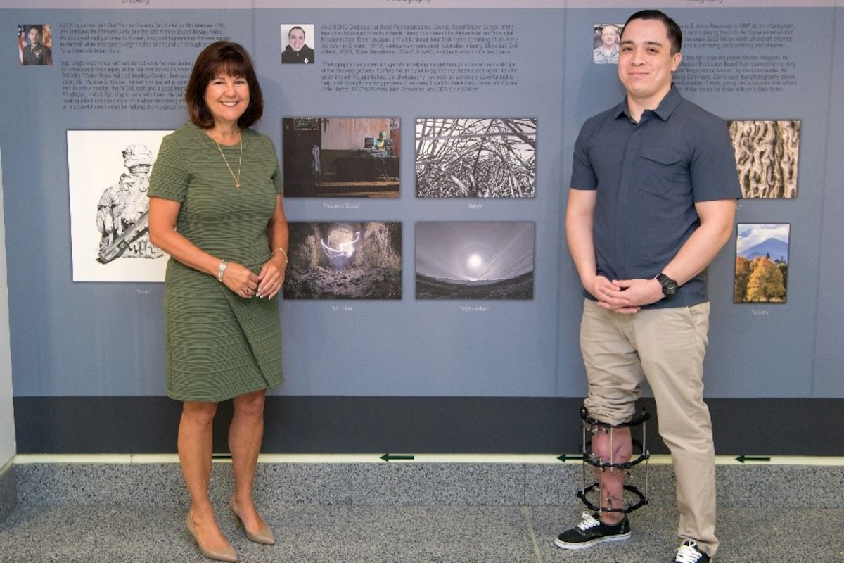 Two people stand next to a display.