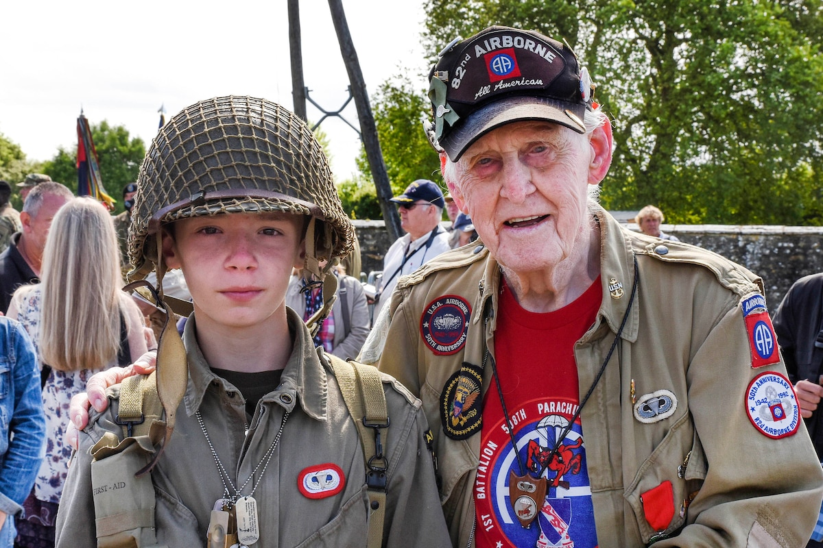 A World War II veteran poses for a picture with a young re-enactor.