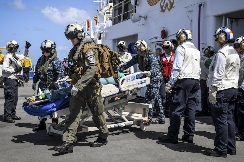 Sailors move a patient on a transport bed.