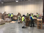 Airmen from the 29th Intelligence Squadron and other volunteers load and arrange supplies at the Red Cross bulk distribution warehouse on Oct. 1, 2017, in Houston, Texas. The Airmen were on permissive temporary duty from Fort Meade, Maryland, to assist as drivers, navigators, key handlers, loaders and inventory managers with Hurricane Harvey relief efforts. (Courtesy photo)