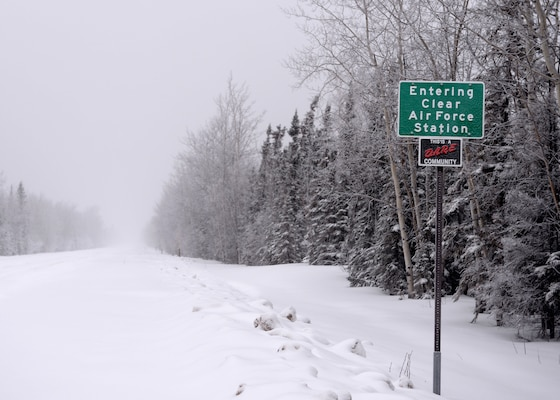 A sign welcoming visitors to Clear Air Force Station stands next to a small road covered in snow.