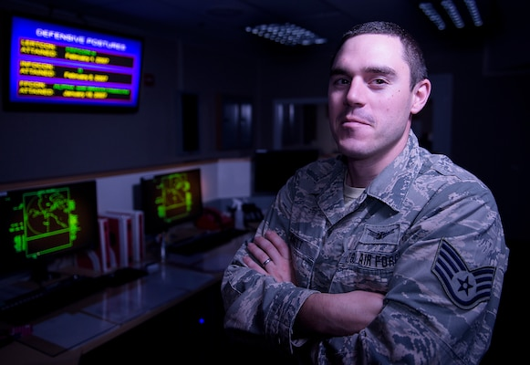 Staff Sgt. Kennett stands in front of displays in the Solid State Phased Array Radar System at Clear Air Force Station, Alaska.