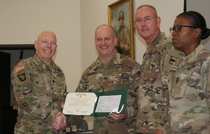 (Left to right) Lt. Col. Kevin Miller, Col. Jay Gilhooly, Command Sgt. Maj. Jeffrey Darlington, and Command Sgt. Maj. Sharon Campbell pose for photographs as Miller receives the 80th Training Command 2017 Instructor of the Year officer award at the completion of the two-day competition at Fort Knox, Kentucky, Oct. 22, 2017.  Miller serves as an instructor for the 100th Training Division-Leader Development.