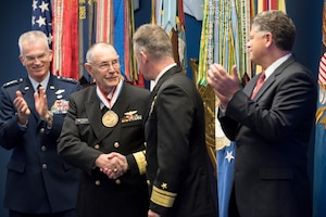 The vice chairman of the Joint Chiefs of Staff claps with others on stage.