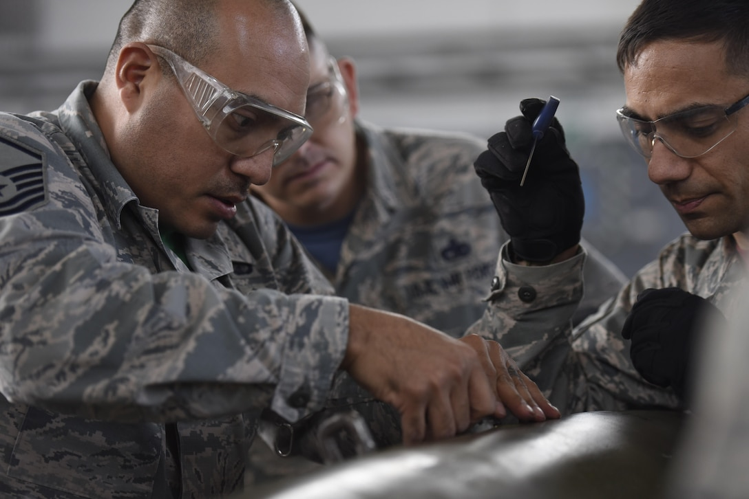 Master Sgt. Ruben Ayala, left, 52nd Contracting Squadron contracting officer, and Master Sgt. Jason Riter, 52nd Maintenance Group first sergeant, work together to build an inert bomb while participating in the 52nd Maintenance Squadron Ammo Rally at Spangdahlem Air Base, Germany, Oct. 20, 2017. Airman from various career fields competed for best time on building an inert bomb. (U.S. Air Force photo by Senior Airman Preston Cherry)